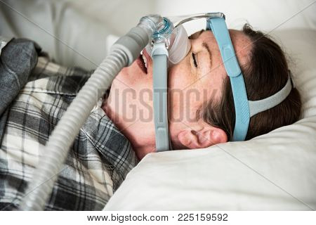 A woman sleeping with anti snoring chin strap