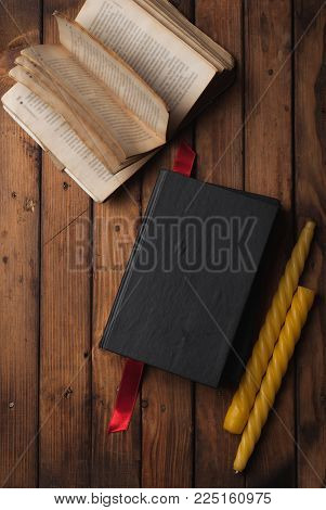 Old books with open pages on wooden background, yellow candle and a red bookmark in a cozy atmosphere