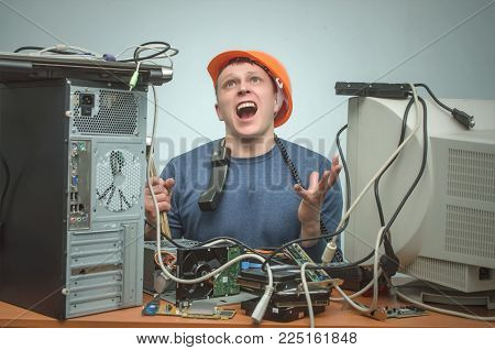Overloaded enraged computer repairman engineer swears into the phone. Computer technician. PC repair service center.