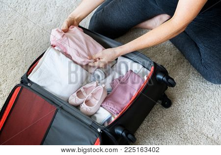 Pregnant woman packing baby stuff for hospital