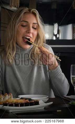 Young blonde woman eat sushi roll at restaurant.