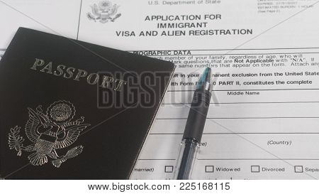 Application for immigrant visa and Alien Registration form and passport with pen