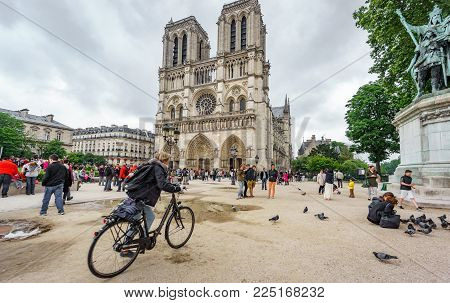PARIS, FRANCE - MAY 15, 2015: Unidentified tourist rides a bike near Notre Dame cathedral with many tourists in Paris, Spain