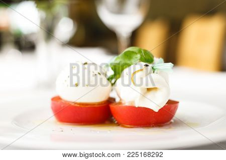 Mozarella cheese with tomatoes and basil in olive oil dressing