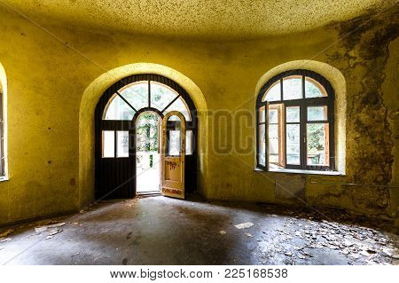 Interior of an abandoned Soviet-era house, yellow walls, parquet and large windows poster