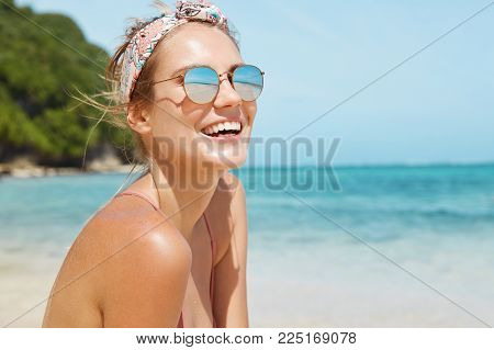 Close Up Shot Of Pleasant Looking Female Wears Headband And Sunglasses, Travels In Tropical Country,