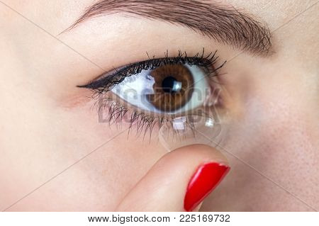 Young woman putting contact lens in her eye close up.