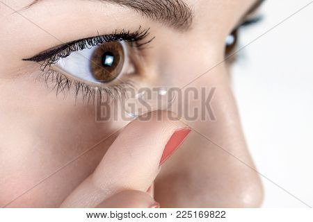 Young woman putting contact lens in her right eye, close up.