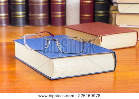 Classic mens eyeglasses lying on the closed book in blue hardcover on a wooden table closeup against of the other books at selective focus