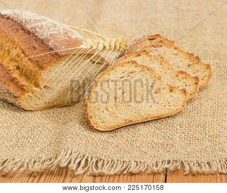 Partly sliced loaf of the wheat and rye sprouted bread with added whole sprouted wheat grains, rye malt and molasses lying on a sackcloth and wheat ear at selective focus