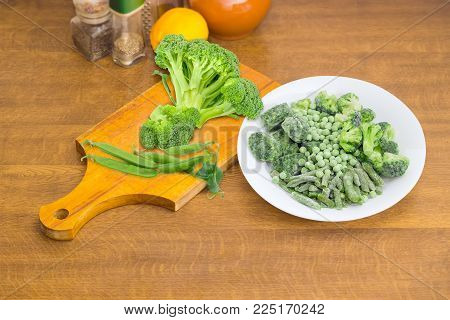 Various frozen green vegetables - green beans, broccoli, cubes of chopped spinach and green peas on white dish, fresh broccoli and pods of green peas on cutting board on cooking table