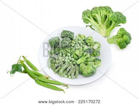 Various frozen green vegetables - green beans, broccoli, cubes of chopped spinach and green peas covered with rime on white dish against of fresh broccoli and pods of green peas on a white background