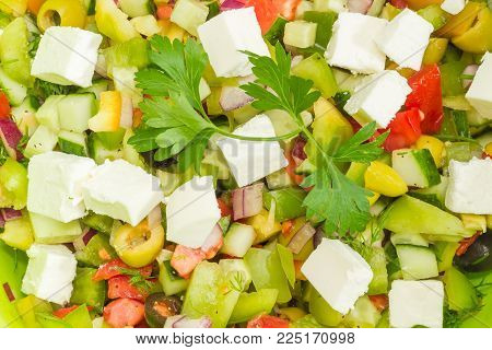 Background of the Greek salad decorated with parsley twig closeup