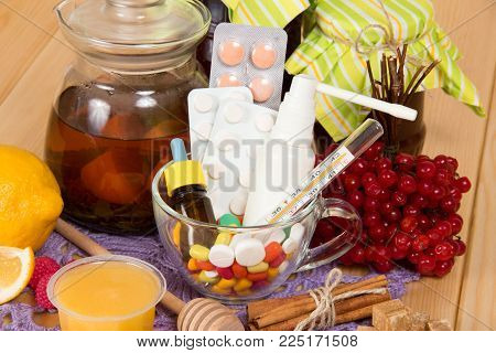 Hot tea with honey and lemon, cup with pills, drops and spray on wooden surface