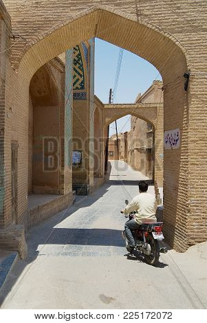 YAZD, IRAN - JUNE 17, 2007: Unidentified man rides motorbike by the narrow street in the historical part of Yazd, Iran.