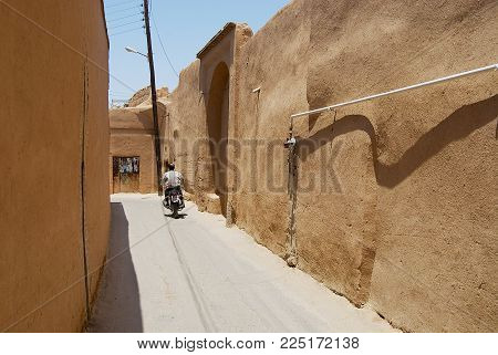 YAZD, IRAN - JUNE 17, 2007: Unidentified man rides motorbike by the narrow street with clay covered walls in the historical part of Yazd, Iran.