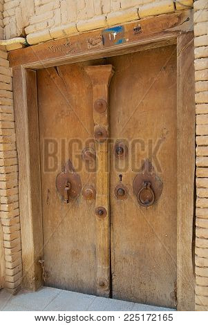 YAZD, IRAN - JUNE 17, 2007: Exterior of a house entrance with the vintage men's and women's door handles in Yazd, Iran.