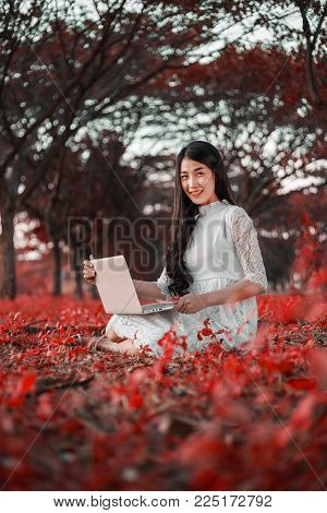 Beautiful Woman Using Laptop In The Park