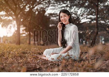 Smiling Woman Talking On Mobile Phone In Park