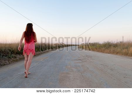 young beautiful girl with long hair in a pink dress barefoot walks along a dirt road from gravel and sand, around her bushes and dry grass, at sunset, the horizon