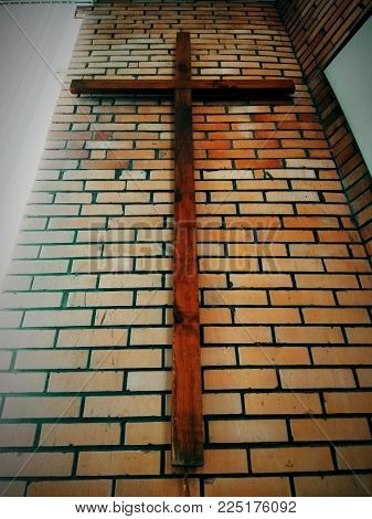 picture of a large wooden Christian Protestant cross hanging on a brick wall of a Baptist church in perspective view.
