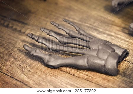 Gray prototype of the human foot skeleton printed on 3d printer on dark surface. Fused deposition modeling, FDM. Progressive modern additive technology. Concept of 4.0 industrial revolution