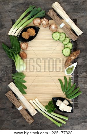 Macrobiotic health food concept with soba and udon noodles, wasabi and miso paste, tofu and fresh vegetables with foods high in protein, antioxidants, vitamins and minerals.