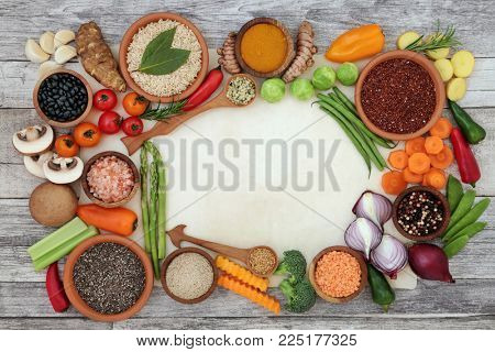 Healthy diet food background border on parchment paper and rustic wood. Super foods concept high in antioxidants, fibre, smart carbohydrates, vitamins, minerals and anthocyanins.