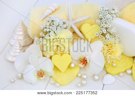 Beauty treatment cleansing  products with heart shaped soaps, orchids and carnation flowers, sponges, wash cloths, shells and decorative pearls on white wood background.