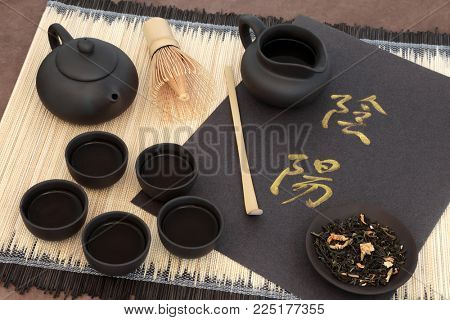 Green jasmine tea with yin and yang chinese calligraphy script, teapot, cups, scoop, whisk and dried leaves on bamboo mat. Translation reads as yin yang.