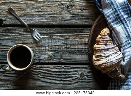 Cup of espresso coffee and croissant in turquoise blue ceramic tray over grey concrete background, selective focus, copy space