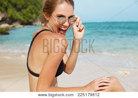 Adorable Young Female Has Fun At Seashore, Glad To Pose At Camera, Looks Through Sunglasses With Joy