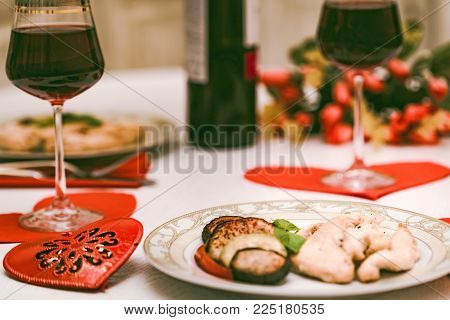 Close up table served for romantic dinner for two with glasses of red wine, roasted chicken fillet with vegetables on plate, red heart and flowers. St.Valentine's concept