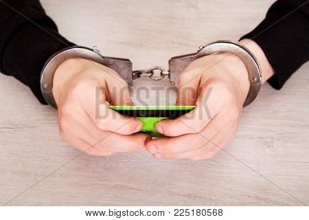 Person in Handcuffs hold a Bank Card on the Table close up