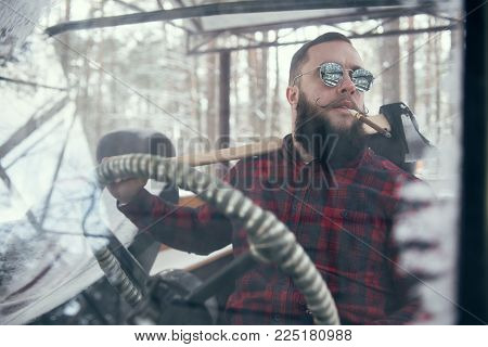 Bearded man with axe in car, smocking cigar. Shallow depth of field