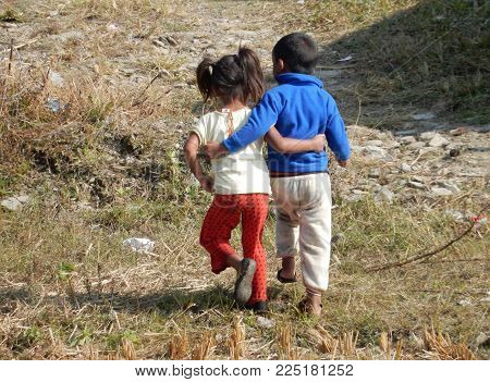 small girl and young boy walking away entwined, Nepal