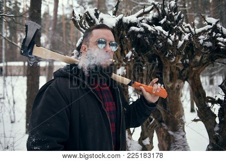 Bearded man with axe in winter outdoors, smocking cigar. Shallow depth of field