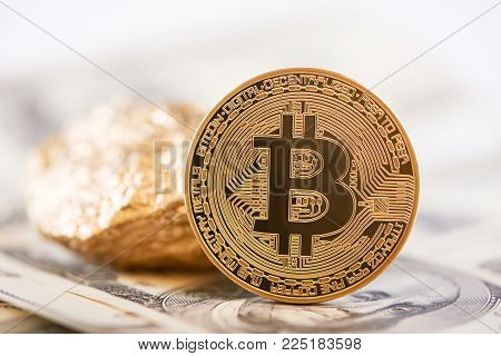 Main cryptocurrency golden bitcoin and gold lump represented on background of dollar banknotes. Digital virtual electronic money web currency futuristic banking finance innovation blockchain