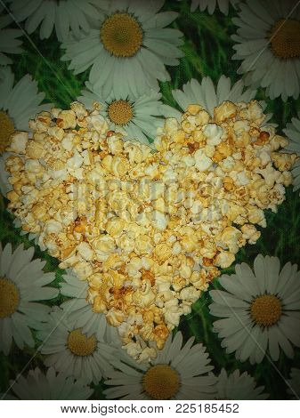 photo yellow appetizing popcorn grains lined in the shape of a heart against a background of chamomiles.