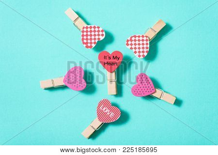 Decoration clothes pegs (heart shape) on green pastel background, Valentine day concept