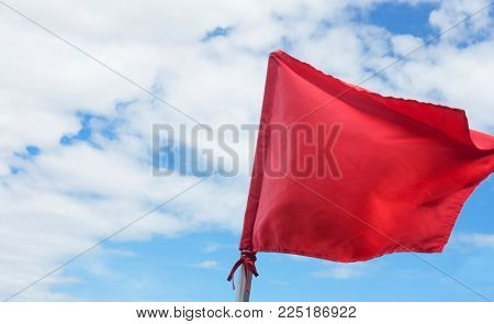 Red Warning Flag Waving On The Blue Sky With Clouds