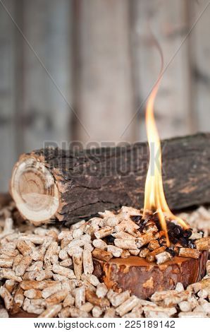 Wooden pellets in fire infront piece of wood