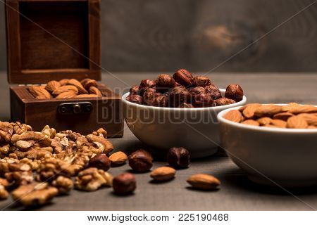 Two white cups with nuts, almonds, hazelnuts, walnut and a wooden box with almonds, side view, on grey wooden table