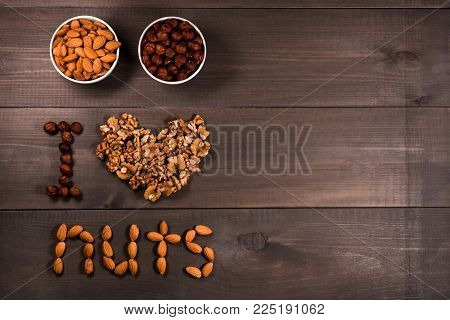 Inscription I love nuts, from nuts, walnuts, almonds and hazelnuts and two white cups with nuts. On brown wooden background.