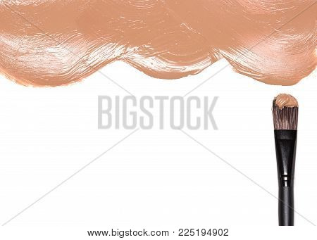 Make-up brush with smeared liquid foundation on white, space for text. Makeup background