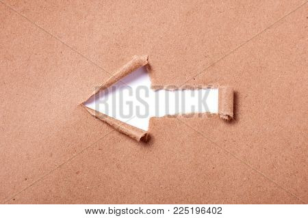 Kraft paper with a hole in the shape of an arrow. Hole isolated on white