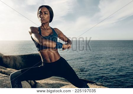 Healthy Woman Stretching Legs Before Running At Seaside