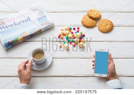 LONDON, UK NOVEMBER 27, 2017: Above view of woman drinking coffee with smartphone in hand. Clipping path