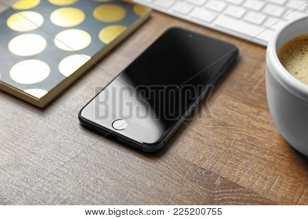 KYIV, UKRAINE - DECEMBER 18, 2017: Modern iPhone 8 Space Gray on wooden table