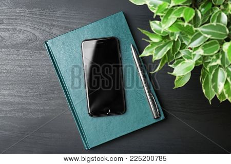KYIV, UKRAINE - DECEMBER 18, 2017: Modern iPhone 8 Space Gray and notebook on table